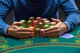 poker-player-taking-poker-chips-winning-sitting-table-close-up-65532209